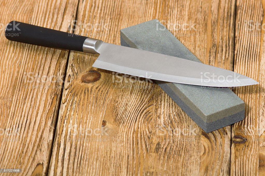 Knife and whetstone on  the wooden board stock photo