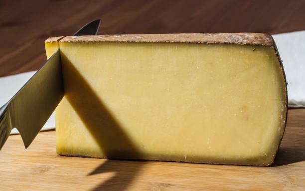 knife cutting a piece of aged comte a famous french cheese - ser comte zdjęcia i obrazy z banku zdjęć