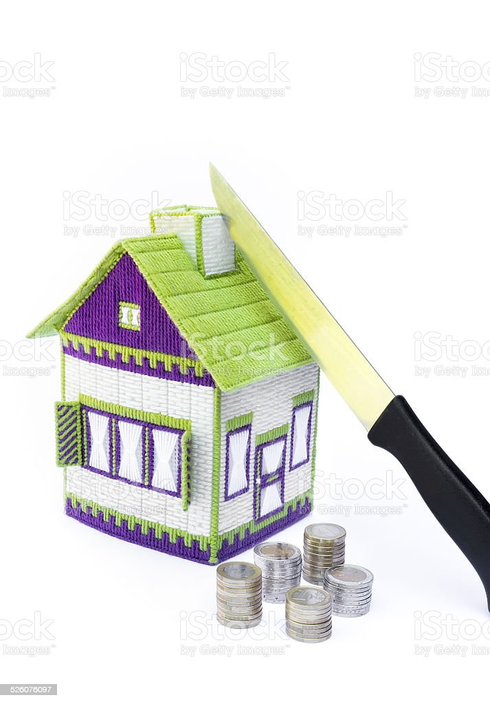 Knife dividing house in two halves stock photo