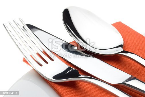 A close up studio shot of a cutlery set on an Orange napkin and china plate with a white background.