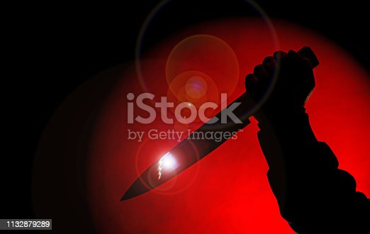 shadow hand holds knife in darkness in red spot light with glows and lens flare