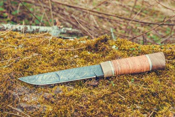 messer aus damast stahl auf grünem moos gefertigt. - damaststahl stock-fotos und bilder