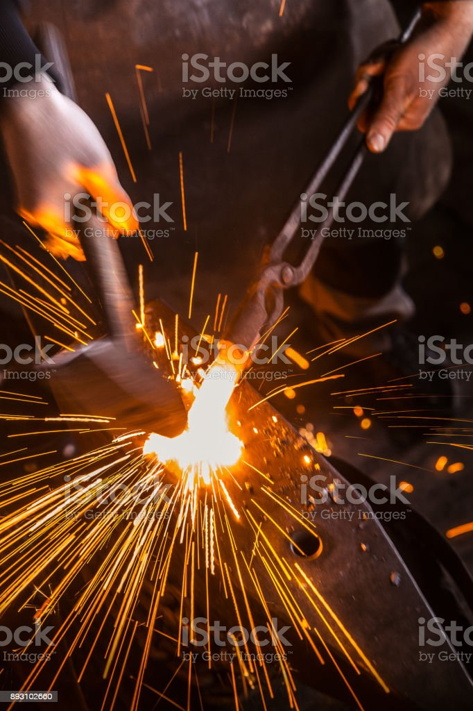 Knife Maker Shaping Hot Piece Of Iron on Anvil With Hammer stock photo