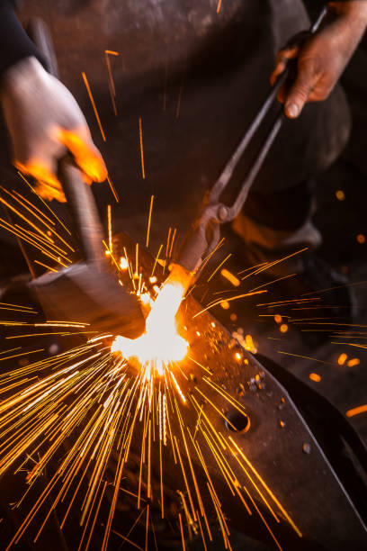 Knife Maker Shaping Hot Piece Of Iron on Anvil With Hammer Knife Maker Shaping Hot Piece Of Iron on Anvil With Hammer anvil stock pictures, royalty-free photos & images
