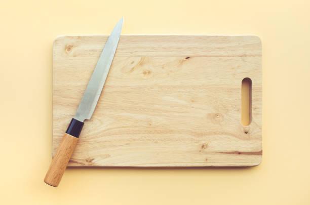 kniv på trä skär bräda på pastellfärgad - bordskniv bildbanksfoton och bilder