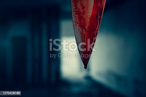 Close up of knife blade with dropping blood