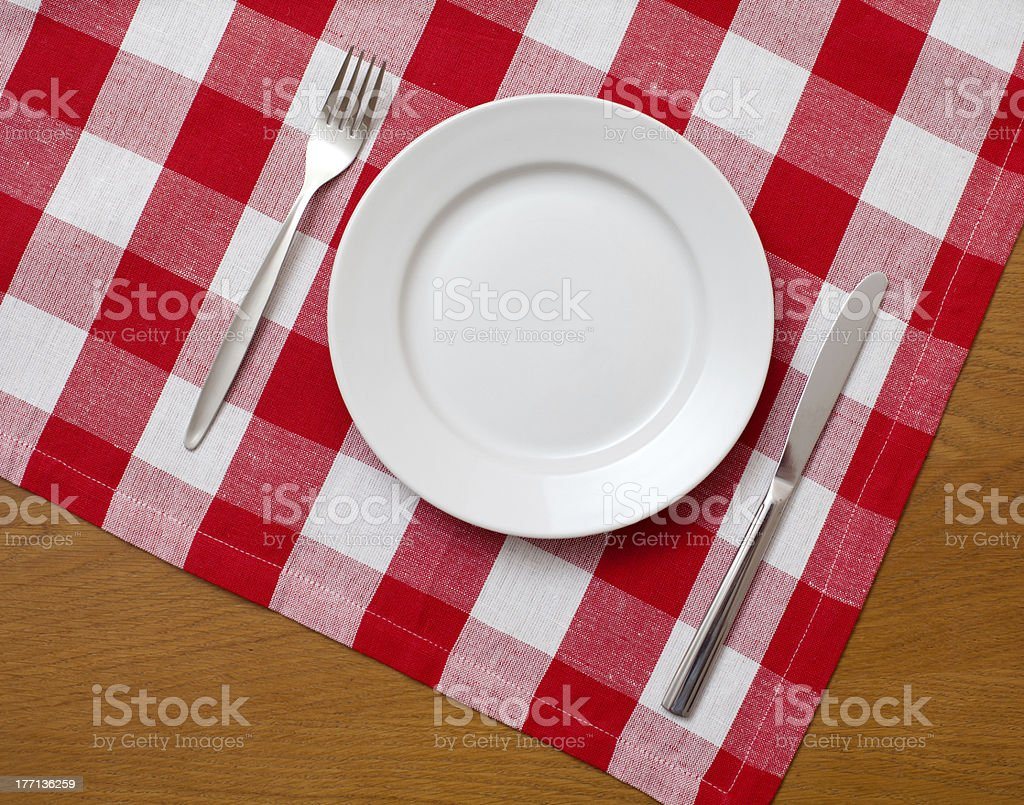 Knife, plate and fork on wooden table with red tablecloth stock photo