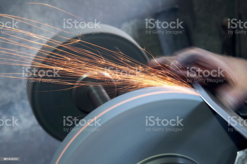 Knife sharpener and hand with blade on  table, closeup stock photo