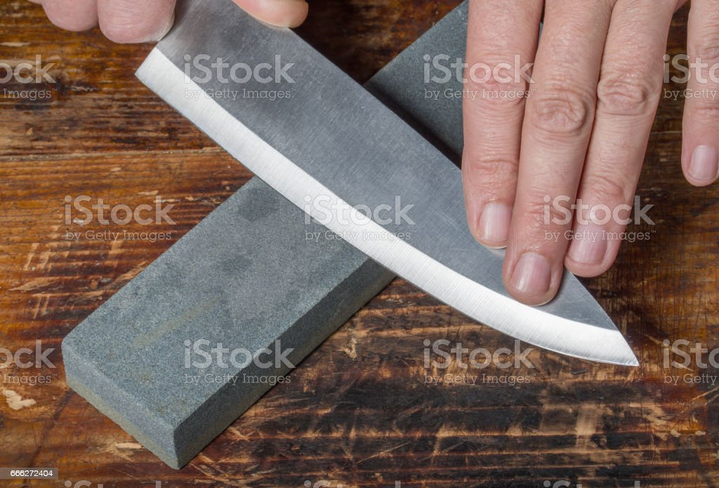 Mes slijpen. Hands Holding mes en Whetstone op de oude houten snijplank. - Royalty-free Apparatuur Stockfoto