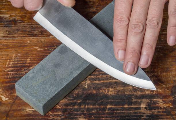 Affûtage de couteaux. Mains retenant le couteau et la pierre sur l'ancienne planche à découper en bois. - Photo