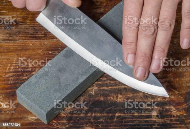 Mes Slijpen Hands Holding Mes En Whetstone Op De Oude Houten Snijplank Stockfoto en meer beelden van Apparatuur