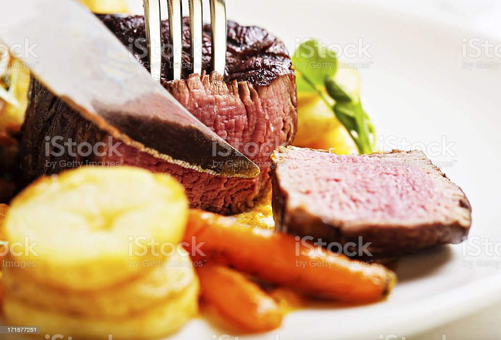 Knife slicing into rare filet mignon in restaurant royalty-free stock photo