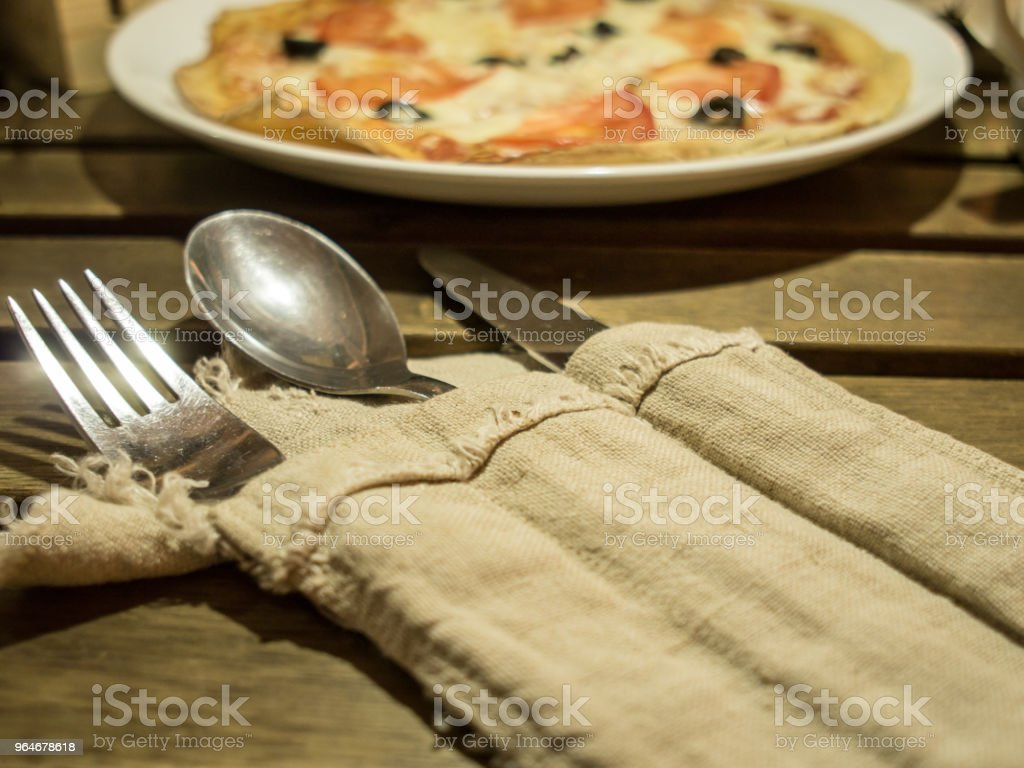 Knife, spoon and fork near dish with pizza on table in cafe royalty-free stock photo