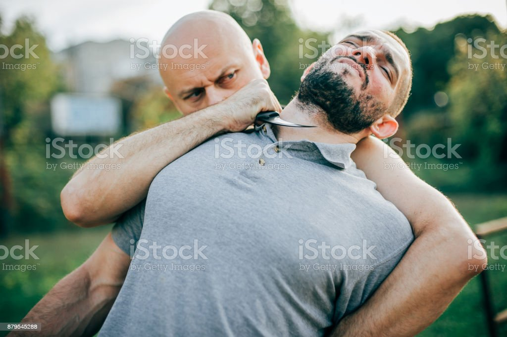 Knife threat. Kapap instructor demonstrates self defense knife threat disarming stock photo