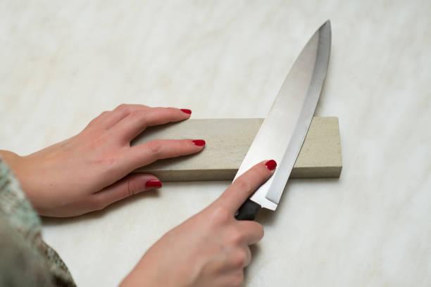 cuchillo, piedra de afilar y manos femeninas - foto de stock