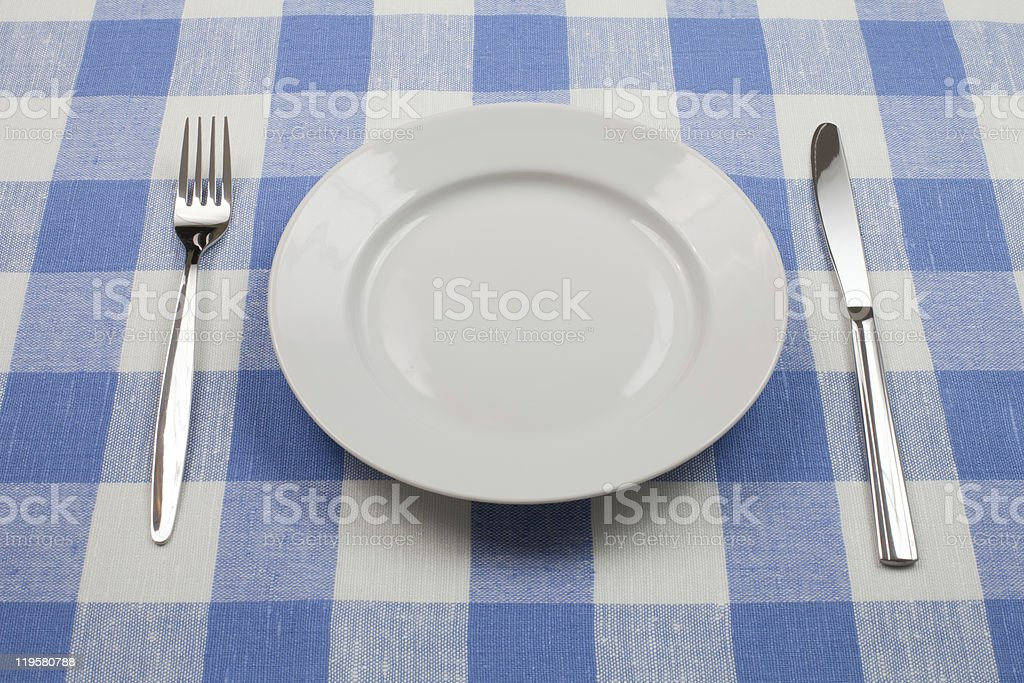 Knife, white plate and fork on blue checked tablecloth royalty-free stock photo