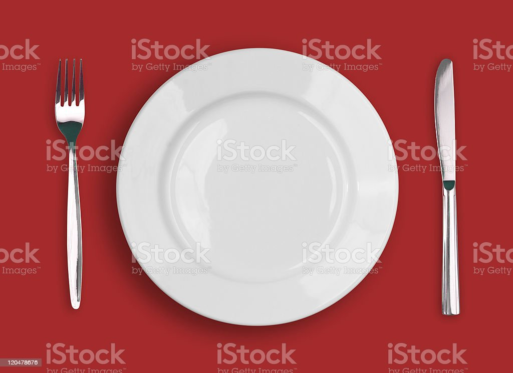 Knife, white plate and fork on red background stock photo