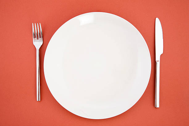 Knife, white plate and fork stock photo