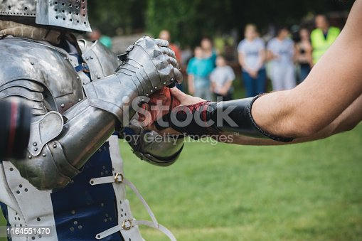 Medieval warrior with body armor on a traditional festival with a squire getting dressed.