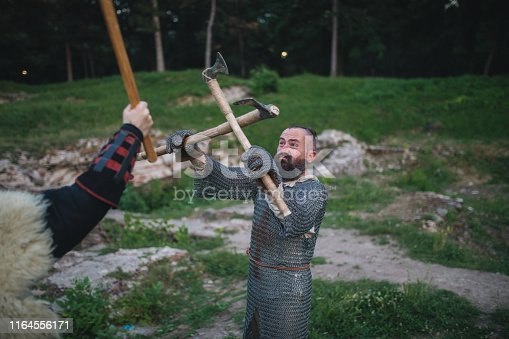 istock Knight defending against axe attack during a fight 1164556171