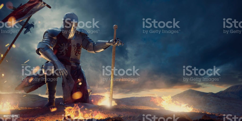 Knight in Amour Kneeling With Sword on Hilltop Near Fire stock photo