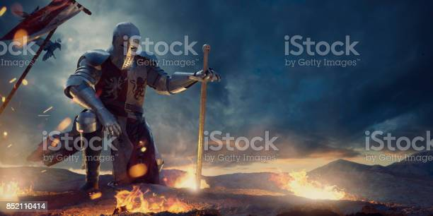 A knight in a full suit of armour, and tabard kneeling with one hand on knee and other resting on sword. The warrior is on rocky high ground surround by small fires of burning debris., with medieval battle flag in the ground behind him, under a dramatic, dark, stormy evening sky.