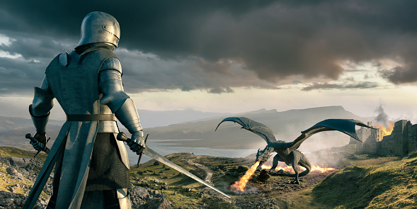 Viewed from behind, a medieval knight shoaled two swords preparing for conflict as he looks down at a large dragon. The fire breathing dragon has wings aloft with grass ablaze behind it. A castle in the background is also on fire. The evening landscape is strewn with rocks and boulders.