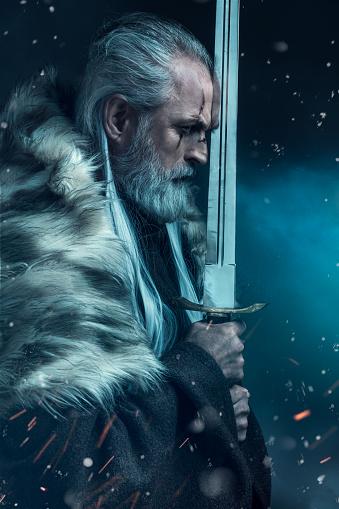 Portrait of senior knight holding big sword