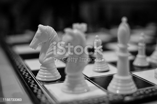 Focus on a kinght piece in a chess game in blsck and white