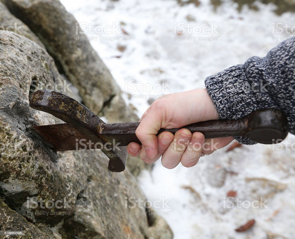 knight tries to remove Excalibur sword in the stone stock photo