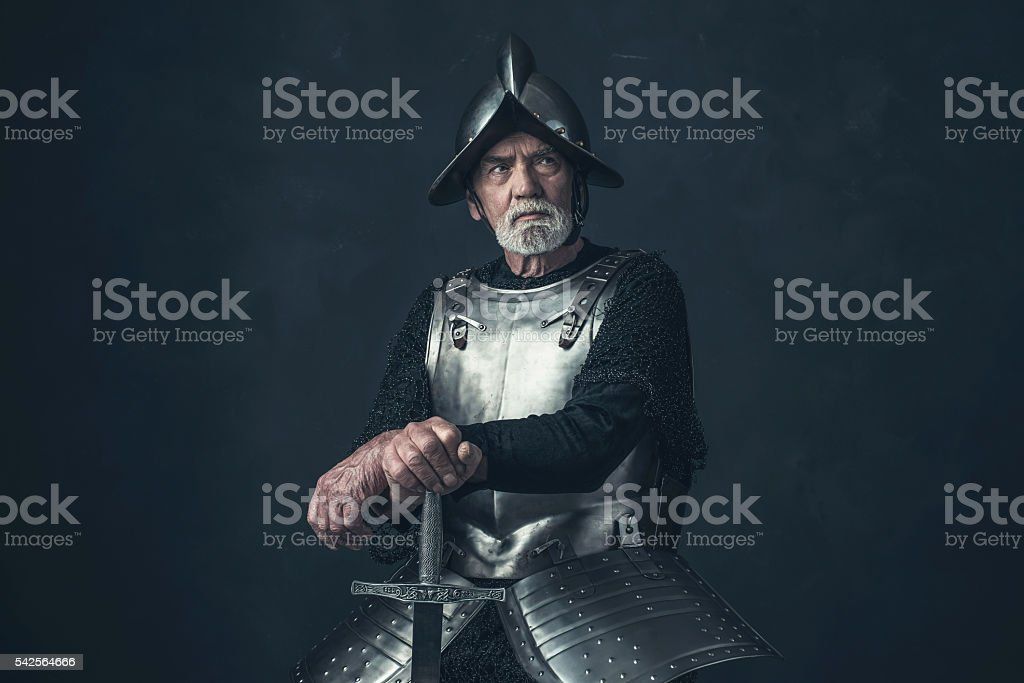 Knight with beard in armor leaning on sword. stock photo