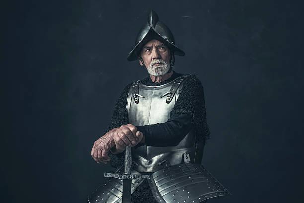 knight with beard in armor leaning on sword. - mittelalterliche ritter stock-fotos und bilder