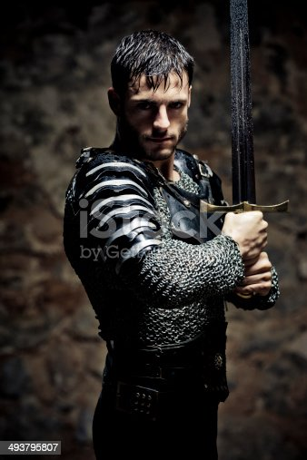 Mystical portrait of medieval Knight with sword ,selective focus, very creative color retouching and hard lighting to underline the ancient medieval time,vignetting and noise