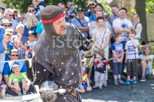istock Knight with Sword, Iron Gloves, Chainmail and Red Headband Fights in Front of the Audience of the Medieval Market 1059523540