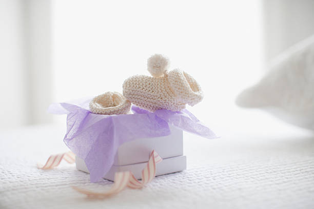 Knit baby booties in gift box stock photo