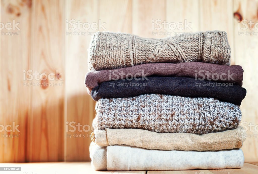 Knit cozy sweater folded in a pile on wooden background .Warm the concept royalty-free stock photo