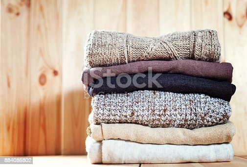 istock Knit cozy sweater folded in a pile on wooden background .Warm the concept 884086802