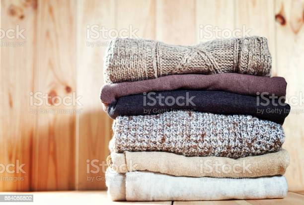 Knit cozy sweater folded in a pile on wooden background warm the picture id884086802?b=1&k=6&m=884086802&s=612x612&h=8z4jdi3yi1yrrvmr4iv5nent901qzo0melhkucu dks=