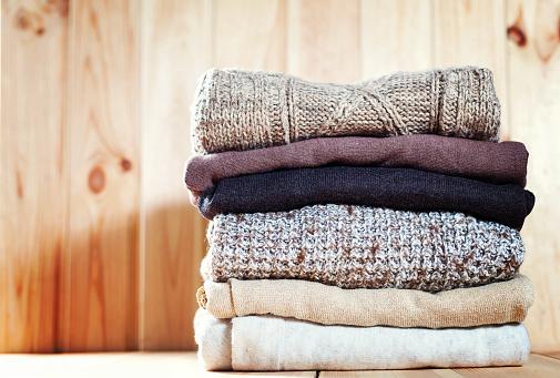 Knit Cozy Sweater Folded In A Pile On Wooden Background Warm The Concept - zdjęcia stockowe i więcej obrazów Akcesorium osobiste