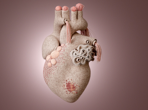 A knit heart with knitting decoration and visible mending