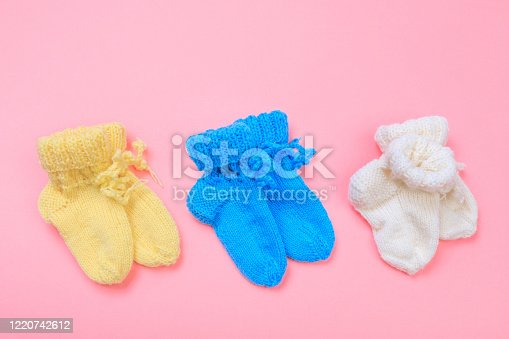 knitted baby booties on pastel pink background - Image
