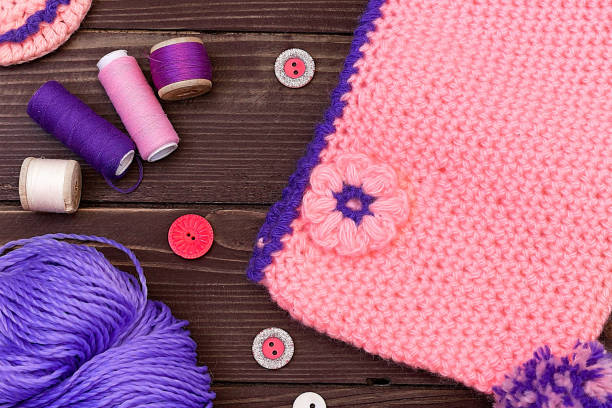 Knitted baby cap and Slippers, yarn for knitting on wooden table. The view from the top. Sewing accessories. stock photo