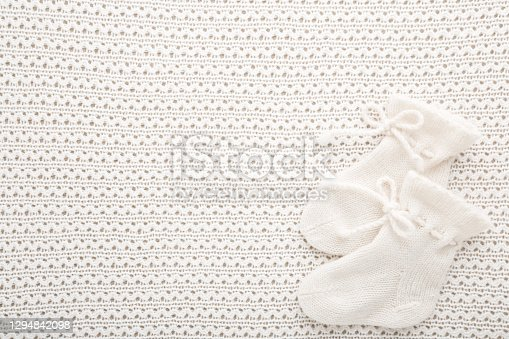 Knitted baby socks on light white blanket background. Closeup. Empty place for text. Top down view.