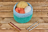 knitted basket with yarn and crochets on a wood background