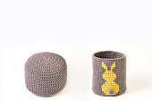 Knitted basket with yellow rabbit and padded stool on white background