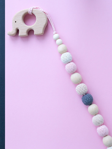 Necklace made from knitted beads and wooden toys for the baby sitting in a sling. Knitted beads.