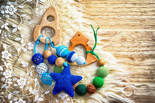 Necklace made from knitted beads and toys for the baby sitting in a sling. Knitted beads. Sling necklace. Spaceship and fir tree. Copy space for your inscription.