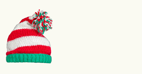 Knitted Christmas hat on a white background. Funny christmas hat. New Year invitation