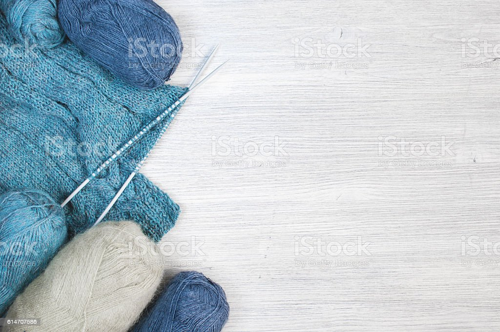 Knitted cloth and skeins of wool on the wooden table stock photo
