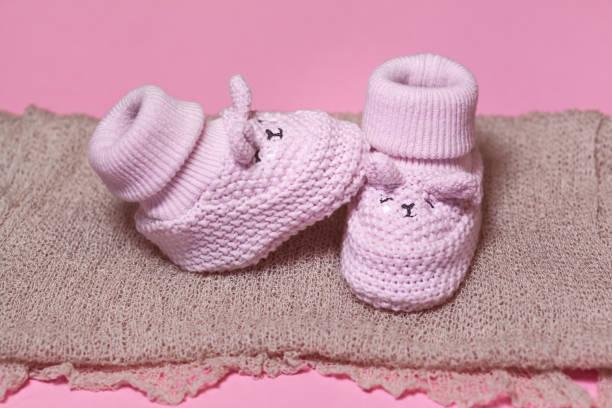 gestrickte häkeln neugeborenen schuhe auf einem rosa hintergrund wartet auf ein baby-mädchen - babyschuhe nähen stock-fotos und bilder